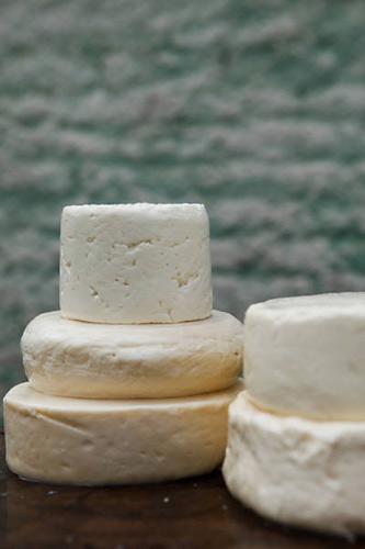 Cinco variedades de queijo de leite cru, de Minas Gerais, sobre bancada de madeira (Foto: Douglas Lambert/Folhapress)